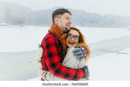Cheerful loving couple is laughing and hugging during the snowfall in the snowy meadow. The beautiful red head girl with glasses.