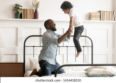 Cheerful loving father having fun with cute little kid jumping on bed, happy african family young dad and small son playing in bedroom, excited black parent child boy feel joy bonding enjoy leisure