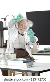 Cheerful mad senior scientist in lab measures green liquid in beaker. Frizzy grey hair, round glasses, lab coat, geek trousers, aqua rubber gloves, blank blackboard, vertical, high key, copy space.