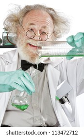Cheerful mad senior scientist in lab measures green liquid in beaker. Closeup, frizzy grey hair, round glasses, lab coat, aqua rubber gloves, vertical, high key.