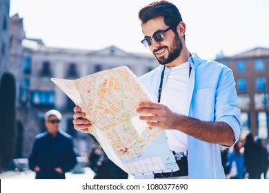 Cheerful mae traveler in stylish sunglasses found right direction on map walking with camera in urban setting.Happy tourist searching showplaces while strolling in city centre during summer trip