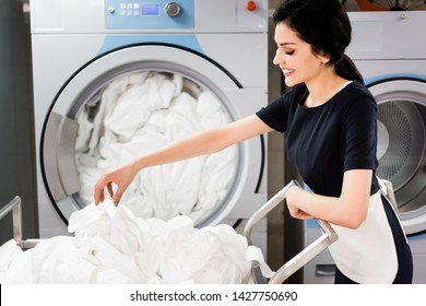 cheerful maid looking at bed sheets while standing near washing machines