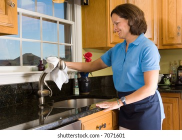 Cheerful maid polishing a brushed nickel faucet in a high end luxury kitchen. Cleaning woman has a smile with eyes focused on the task at hand.