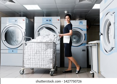 cheerful maid standing near metallic cart with bedding in laundry