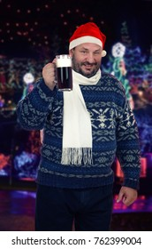 Cheerful male beer lover winks at camera toasting with pint of dark beer. Middle-aged man wearing winter sweater, white scarf and red Santa Claus hat stands on Christmas outdoors blurred background