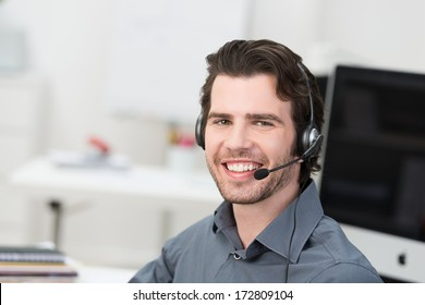Cheerful male call centre operator or businessman wearing a headset sitting in an office grinning happily at the camera