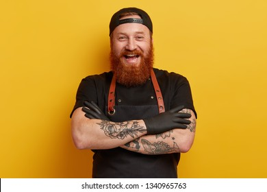 Cheerful male chef in black apron, t shirt and gloves, has thick long ginger beard, keeps arms folded, laughs sincerely, has break after cooking, talks with colleagues in restaurant, shares new recipe