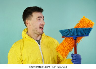 Cheerful male cleaner with a mop and a broom in his hands in rubber stoves. Blue background. Cleaning concept
