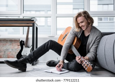 Cheerful male composer is writing song in notebook. He is holding guitar and smiling