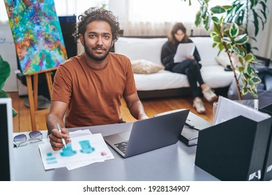 Cheerful male designer with curly hairs in casual attire sits at table and designing concept of shirts using a laptop and a pen.