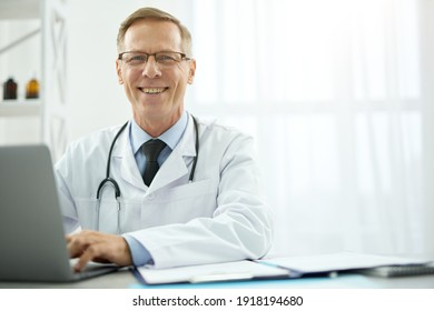 Cheerful male doctor sitting at the table with laptop in clinic