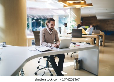 Cheerful male entrepreneur in casual wear sitting at table in modern coworking space and working on netbook on background of busy group of diverse people