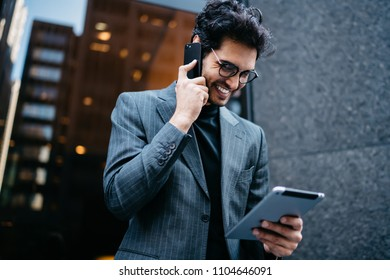 Cheerful male executive manage in formal wear satisfied with good news talking on smartphone and checking mail on touchpad outdoors, prosperous businessman using portable pc for banking via app