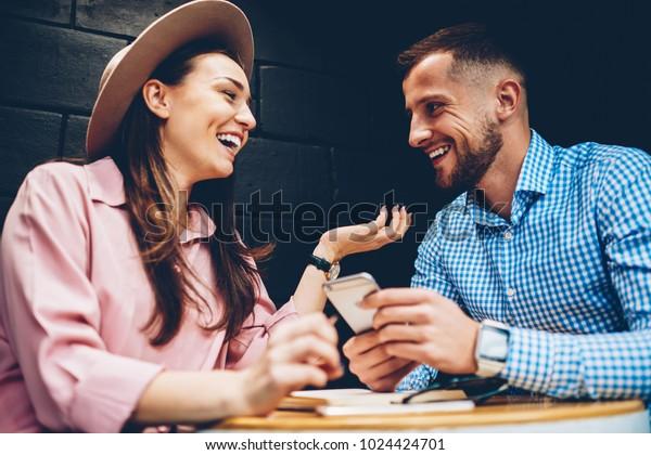 カフェでの会議中に、一緒に自由な時間を楽しみ、ネットワークでマルチメディアを共有し、デート中に笑うロマンチックな夫婦、おかしな写真を見る楽しい男女の友達