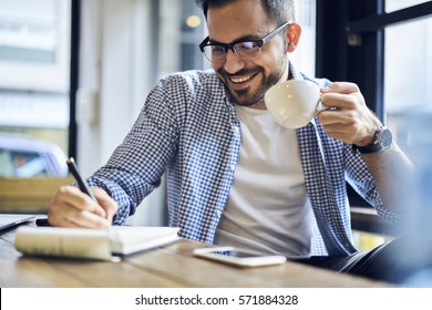 Cheerful male journalist in trendy glasses happy to finishing work on book review rereading written in notebook text before calling to editor to present publication drinking coffee for lunch in cafe