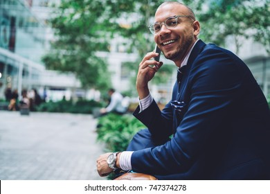 Cheerful male manager in formal wear discussing successful project with colleague during phone talk,prosperous entrepreneur in eyeglasses having mobile conversation about business near publicity area
