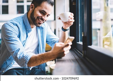 Cheerful male person happy to receive messages from friend checking mail via smartphone during rest in cafe, smiling man satisfied with getting good news using telephone fr networking drinking coffee