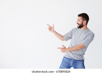 Cheerful male pointing with both hands on white field aside, bending back a bit, wearing grey T-shirt, mid shot