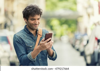 Cheerful male in the street texting on Mobile phone. Connection device