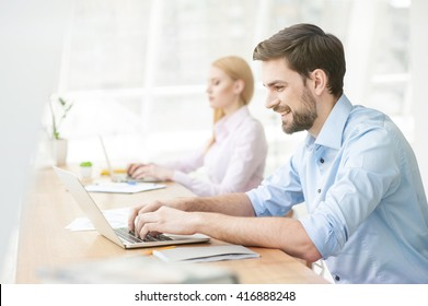 Cheerful male student is working on computer