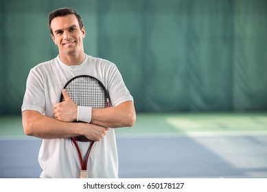 Cheerful male tennis player enjoying game