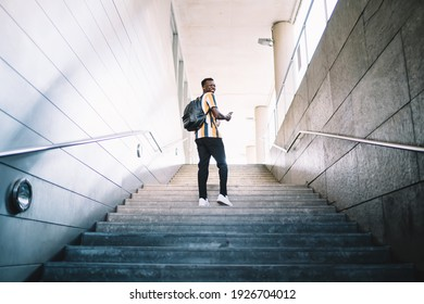 Cheerful male tourist dressed in stylish fashion outfit smiling during sightseeing time in travel city, back view of happy African American student with trendy backpack climb urban stairs