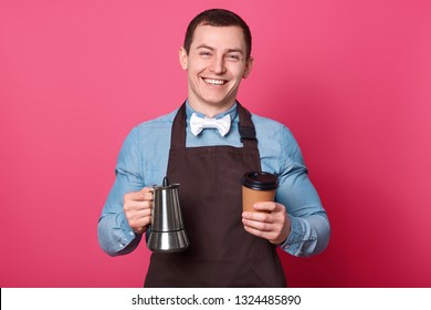 Cheerful male waiter holds coffeemaker and paper cup, prepares nice drink for visitors in cafe, has broad smile, white teeth, dressed in shirt with bowtie and apron, isolated over pink background