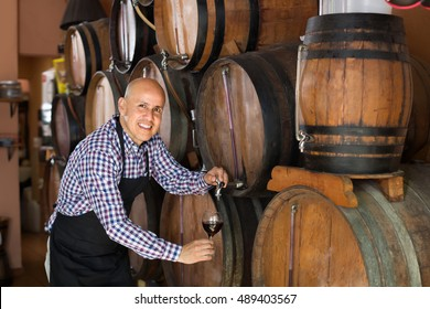 Cheerful male wine maker taking wine from wood in winery