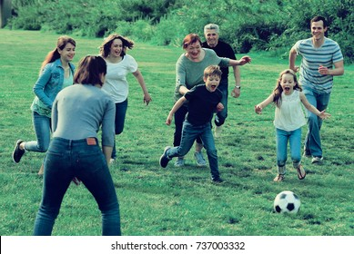 Cheerful males and females kicking the ball on green lawn