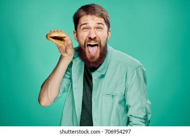 cheerful man with beard in shirt shows tongue in camera in hand cheeseburger on green background, fast food