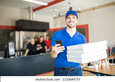 Cheerful man in blue t-shirt and cap holding smartphone and delivery boxes in restaurant looking at camera