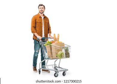 cheerful man carrying shopping trolley with products in paper bags isolated on white