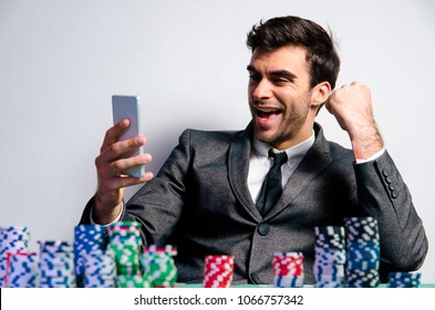 Cheerful man celebrating online poker win, playing on smartphone ; poker apps concept