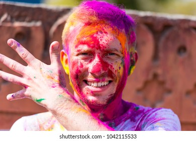 Cheerful man in colored t-shirt during Color Holi festival