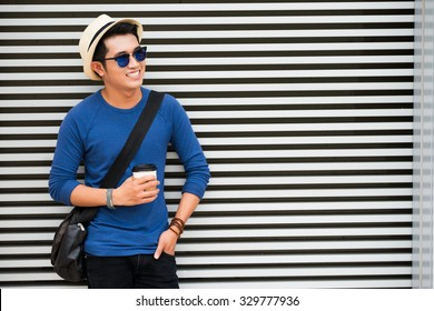 Cheerful man with crossbody bag and take-out coffee standing at the striped wall