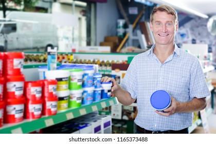 cheerful man customer choosing paint bucket in housewares hypermarket