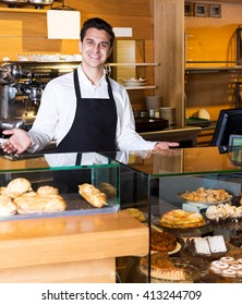 Cheerful man with delicious cream pies at bakery display