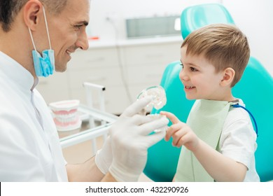 Cheerful man dentist talking to little boy and demonstrating tooth brushing