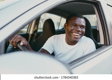 Cheerful man driving a car African appearance smile ride