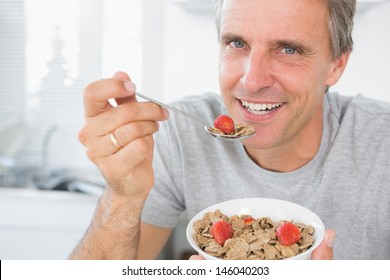 Cheerful man eating cereal for breakfast looking at camera
