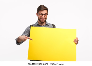 Cheerful man in glasses pointing at yellow placard on white background.