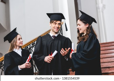 cheerful man in graduation cap gesturing near attractive girls while holding diploma
