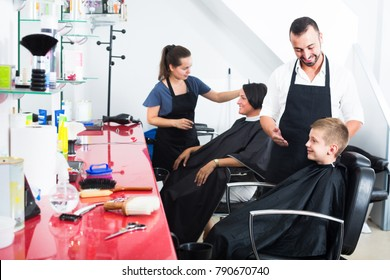 cheerful man hairdresser cutting hair of schoolboy sitting in chair in beauty salon . Focus on boy