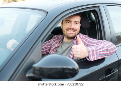 Cheerful man in his new car and thumb up gesture
