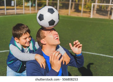 Cheerful man is holding ball on his head with concentration. He son is embracing him and smiling