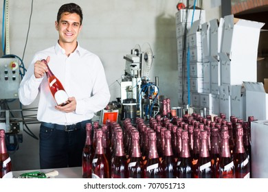 Cheerful man holding bottle of wine in packing  section of wine factory