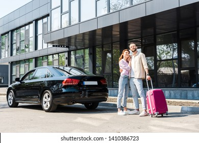 cheerful man hugging happy woman while standing near black car with pink luggage