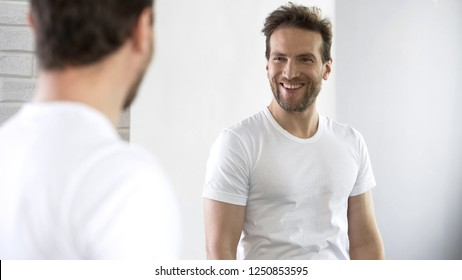 Cheerful man looking at reflection in mirror, motivating for success during day