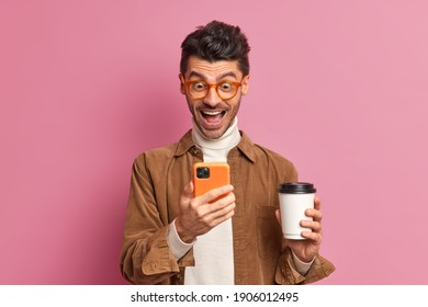 Cheerful man looks gladfully at smartphone screen reads funny news drinks takeaway coffee wears optical glasses brown shirt poses indoor against pink background. People emotions technology concept