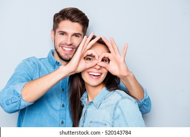 Cheerful man making glasses to his girlfriend with fingers